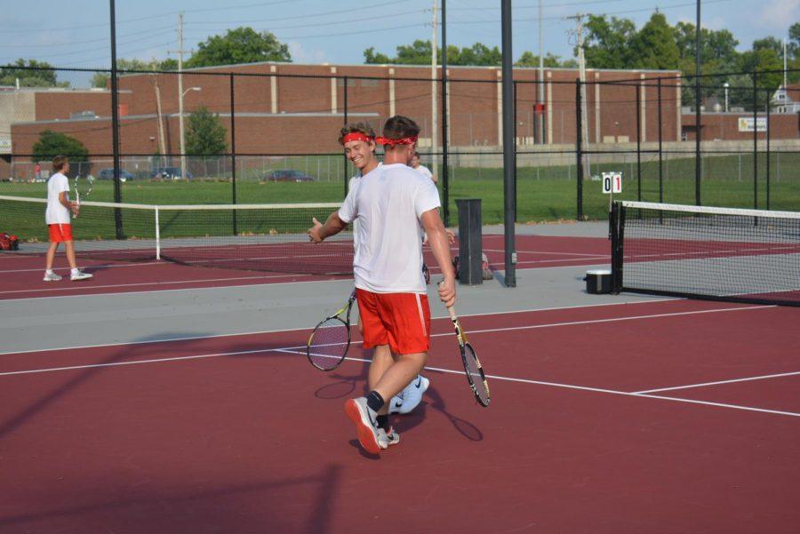 Junior+Cody+Medley+high+fives+his+doubles+partner+senior+Ben+Stock.