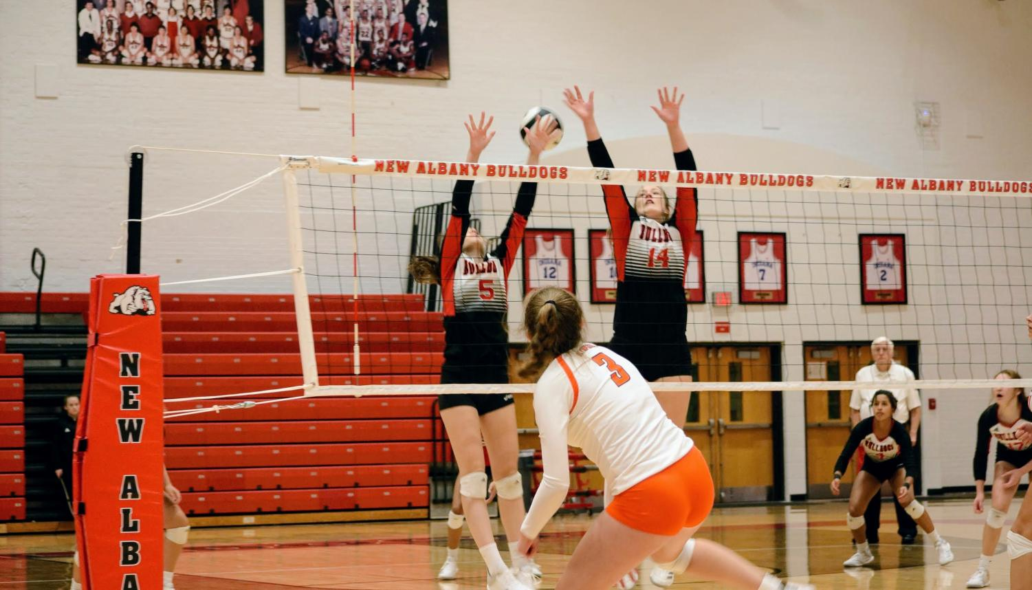 Junior Savannah Meyer (5) jumps with junior Dani Grant (14) to block the spike.