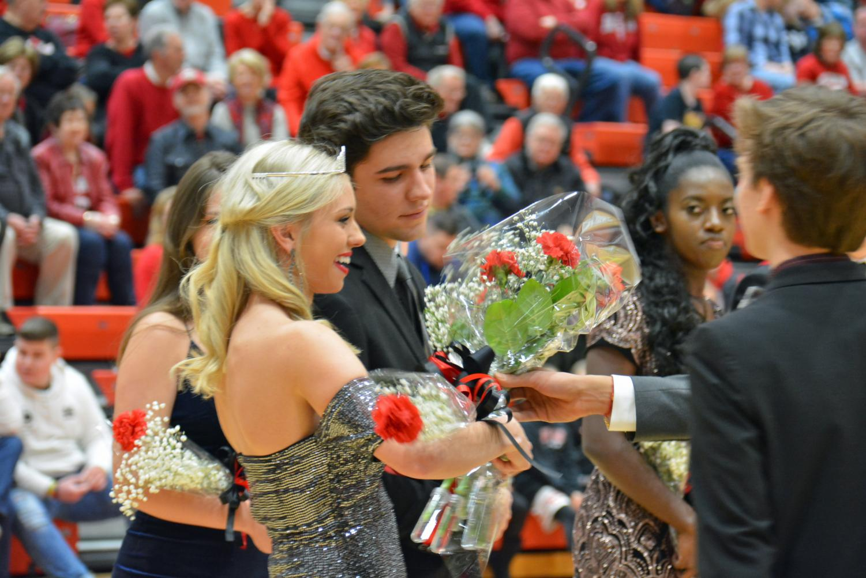 Olivia Hawkins receives a bouquet from Vijay Chirmumilla.